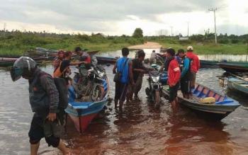 Para pengguna roda dua menggunakan jasa getek untuk melalui titik banjir di jalan Kolam Km 38.