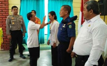 PLH Kepala BPBD Kotim Senddy saat mengalungkan tenda peserta kepada sejumlah masyarakat yang ikut dalam pelatihan tersebut, Rabu (26/7/2017).