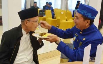 Bupati Barito Utara, Nadalsyah memberikan suapan potongan tumpeng pertama ke mantan Bupati Barito Utara periode 1988–1998, Drs H A Dj Nihin