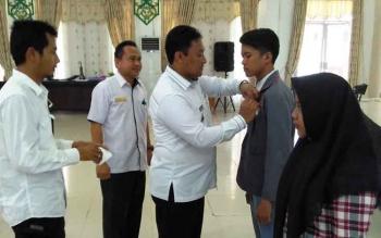 Bupati Pulang Pisau didampingi Kepala DPMD saat menyematkan tanda peserta kepada peserta lomba teknologi tepat guna di Pulang Pisau, Rabu (26/7/2017)