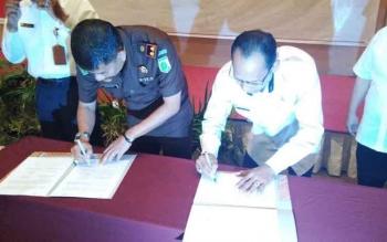 Kepala Kejaksaan Negeri Gunung Mas Koswara (kiri) menandatangani MoU dengan BPJS Kesehatan Cabang Palangka Raya, Rabu (26/7/2017).