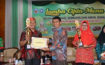 Bupati Mura, Perdie M Yoseph saat menyerahkan tropi juara pertama pada Lomba Cipta Menu tingkat Kabupaten Mura, Kamis (27/7/2017).