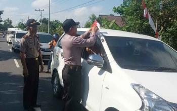 Kapolsek Basarang AKP Darwin bersama anggotanya sedang memasang bendera di mobil yang melintas, Kamis (27/7).