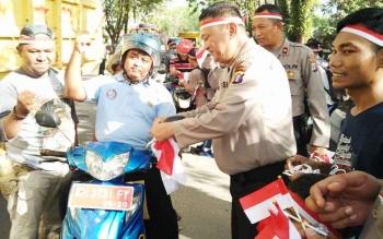 Kapolres Kotim AKBP Muchtar Supiandi Siregar bersama sejumlah anggotanya dan komunitas motor di Kota Sampit saat membagikan bendera di perempatan bundaran depan Polres Kotim, Jumat (28/7/2017) sore.