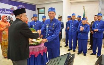 Bupati Barito Utara Nadalsyah menyerahkan potongan tumpeng pertama pada peringatan hari jadi Kabupaten ini kepada bupati pendahulunya, A Dj Nihin.