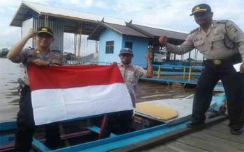 Polsek Pahandut Bagikan Bendera Merah Putih Sampai ke Tepian Sungai