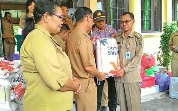 Plt Bupati Katingan Sakariyas menyerahkan bantuan beras kepada Camat Katingan Hilir Ardiansyah untuk selanjutnya dibagikan kepada warga yang terkena bencana banjir, Senin (31/7/2017).
