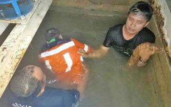 Anggota Polsek Laung Tuhup beserta rekan kerja korban ketika mengevakuasi mayat Fernando yang ditemukan di dalam tong penampungan air, Minggu (30/7/2017) malam.