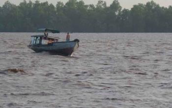 Sebuah perahu kelotok yang melayani penyeberangan dari Kecamatan Mentaya Hilir Selatan menuju Pulau Hanaut saat melintasi Sungai Mentaya yang ombaknya cukup tinggi.