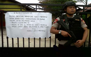 Aparat kepolisian berjaga-jaga di pintu gerbang SDN 1 Mentang. Nampak pemberitahuan pengumuman terpasang di sampingnya.
