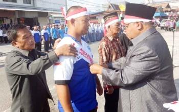 Bupati Sukamara, Ahmad Dirman saat menyematkan tanda anggota Satgas.