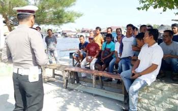 Kasat Lantas Polres Sukamara, Iptu Amzi Halim Permana saat menyampaikan sosialiasi aturan berkendara kepada tukang ojek dan supir travel di pelabuhan speet boat.