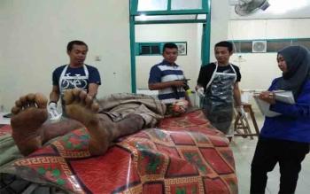Petugas kamar jenazah dan dokter sedang memeriksa jenazah pria yang ditemukan tewas di dalam kamar barak, Selasa (1/8/2017) malam.