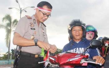 Kapolres Lamandau, AKBP Andika Kelana Wiratama, saat membagikan bendera merah putih gratis sekaligus memasangkannya di salahsatu ranmor warga, baru-baru ini.