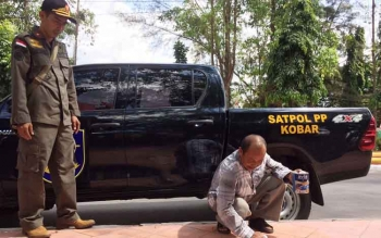 Dengan diawasi oleh anggota Satpol PP Kobar, Sudarsono (55) diberikan sanksi sosial dengan membersihkan trotoar yang di coretnya, Rabu (2/8/2017).