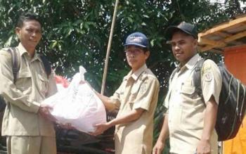 Camat Kamipang Sukarti (tengah) secara simbolis menyerahkan paket sembako bantuan dari Gubernur Sugianto Sabran kepada salah satu kepala desa
