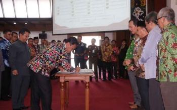 Bupati Pulang Pisau Edy Pratowo didampingi Ketua DPRD Kabupaten Pulang Pisau saat menandatangani komitmen bersama pemberantasan korupsi.