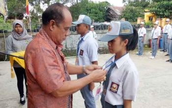 Kepala Disparpora Kabupaten Gunung Mas, Suprapto Sungan memsang tanda peserta kepada calon anggota Paskibraka yang mengikuti pembinaan dan pelatihan