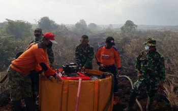 Sejumlah petugas sedang berusaha mengisi air untuk melakukan pemadaman kebakaran hutan.