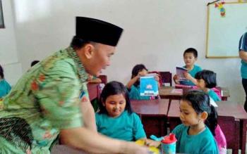 Gubernur Kalteng Sugianto Sabran membagikan buku ke murid SDN 1 Langkai.