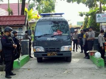 Aparat kepolisian berjaga di sekitar di SDN 5 Langkai, Kota Palangka Raya, yang menjadi lokasi rekonstruksi kasus pembakaran sekolah, Jumat (4/8/2017). Setelah selesai, polisi langsung membawa tersangka pembakar sekolah ke Polda Kalteng.