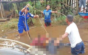 Sejumlah aparat dan warga mengevakuasi jasad pria tanpa identitas yang ditemukan tewas di tepi Sungai Mentaya.