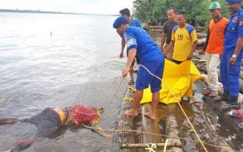 Petugas dan warga mengevakuasi mayat tanpa identitas yang ditemukan mengapung di Sungai Mentaya, kawasan Desa Pelangsian.