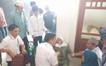 Petugas kesehatan saat menangani Baimah (59) yang kritis saat akan diberangkatkan di Halaman Masjid Agung Al-Istiqlal, Selasa (8/8/2017).