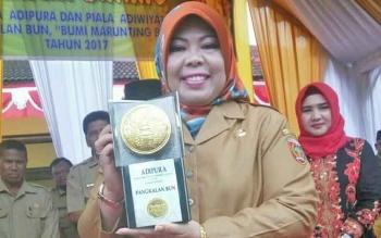 Bupati Kobar Nurhidayah sedang membawa piala Adipura Buana 2017