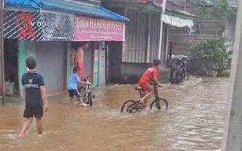 Sejumlah anak sedang bermain di jalan yang terendam banjir, beberapa waktu lalu.