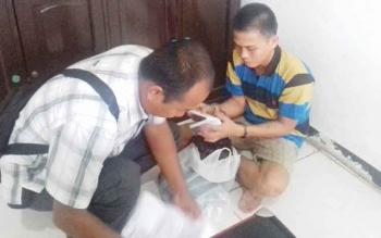 Banjir alias Anjir tersangka kasus pembunuhan (duduk) saat memperlihatkan surat penahanannya kepada pihak kepolisian.