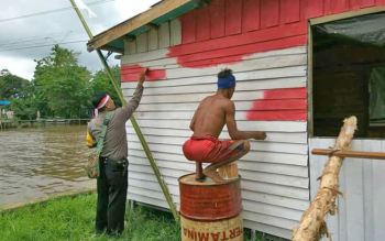 Bhabinkamtibmas Kelurahan Pulau Kupang Aiptu Taufik Hidayat bersama dengan Kanit Binmas Polsek Selat Aiptu Danuri mengecat Poskamling bersama warga Desa Pulau Mambulau.