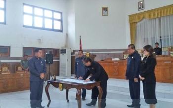 Ketua DPRD Kabupaten Gunung Mas Gumer menandatangani nota pengesahan dua raperda menjadi perda pada Rapat Paripurna, Rabu (9/8/2017).