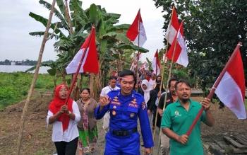 Kasatrolda AKBP Sulistiyono bersama ratusan warga dan siswa sekolah saat melakukan pawai bendera di Desa Ganefo, Kecamatan Seranau, Kabupaten Kotawaringin Timur (Kotim), Rabu (9/8/2017).