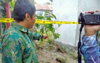Heri Purwanto menunjukan pohon yang dipotong dan disiram minyak tanah. Lokasi sekitar sudah dipasang garis polisi.