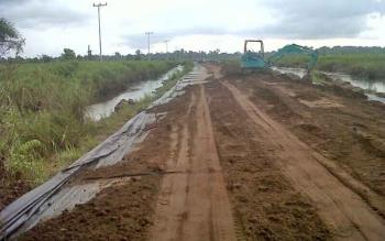 Sebuah alat berat berada di jalan menuju Desa Talingke untuk meratakan timbunan tanah di jalan itu, Senin (4/8/2017).