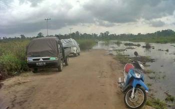Beberapa kendaraan parkir di jalan arah menuju Desa Talongke yang terendam banjir, Senin (14/8/2017). Warga berharap banjir cepat surut agar penimbunan jalan lancar.