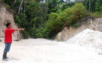 Seorang warga menunjuk lokasi galian C di Desa Sababilah