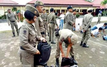 Anggota satpol pp memeriksa tas para siswa