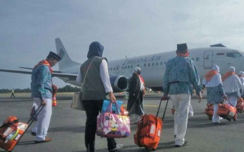 Jemaah calon haji asal Kabupaten Kotawaringin Barat berjalan menuju pesawat Trigana Air di Bandara Iskandar Pangkalan Bun, Selasa (15/8/2017).