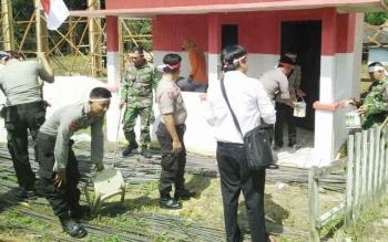 Kapolsek Permata Kecubung, Ipda Maulana Rahmat Al Haqqi dan bersama beberapa anggotanya saat melakukan pengecatan pos kamling di Desa Ajang.