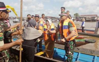 Komandan Kodim 1014/Pbn Letkol Inf Wisnu Kurniawan dan Bupati Kobar Hj Nurhidayah saat menyambangi warga Raja Seberang untuk membagikan bendera dan sembako.