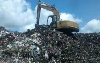 Sebuah alat excavator sedang menumpuk sampah di tempat pembuangan akhir (TPA)