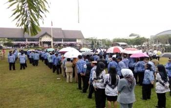 Peserta upacara HUT RI ke-72 di halaman balai Kota Palangka Raya ada yang menggunakan payung agar tidak basah kena air hujan, Kamis (17/8/2017)
