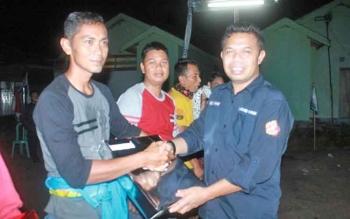 Ketua Karang Taruna Kalimantan Tengah, Abdul Hafid (kanan) menyerahkan hadiah kepada juara pertama lomba tarik tambang, Kamis (17/8/2017) malam.