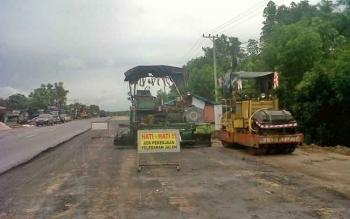 Alat berat yang digunakan mengaspal jalan ini masih belum dioperasikan karena masih terkendala hujan, Sabtu (19/8/2017)