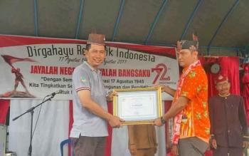 Bupati Barito Utara Nadalsyah saat menerima penganugerahan gelar kehormatan dari ketua DAD Kecamatan Gunung Timang, Senin (21/8/2017).