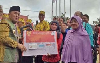 Gubernur Sugianto saat menyerahkan kartu KIS disela peringatan HUT ke-15 Bartim, Rabu (23/8/2017).