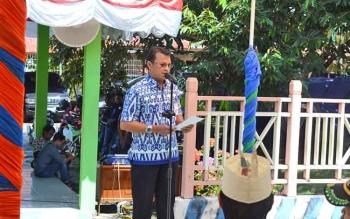 Asisten I Sekda Barito Utara Jufriansyah membacakan sambutan Bupati Nadalsyah saat penyerahan alsintan kepada kelompok tani, Kamis (24/8/2017).