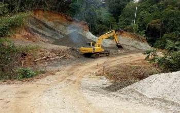 Sebuah alat excavator sedang mengerjakan peningkatan ruas Kuala Kurun-Desa Sare Rangan